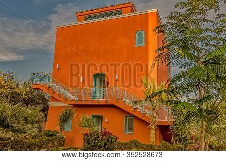 A Square Red Ocher-clored House Among Palms In The Sunshine Against A Blue Sky, El Gouna, Egypt, Jan