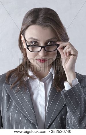 Young Attractive Businesswoman Looks Right To The Camera Through Glasses With Ironic Expression. Dar