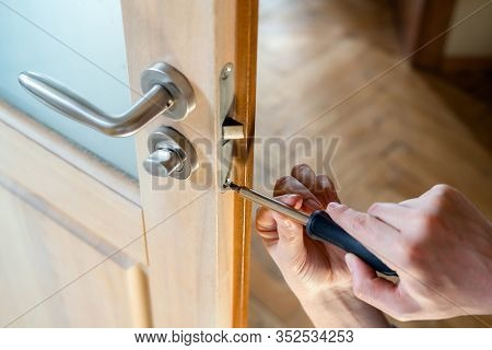 Carpenter Repairing Door Lock. Installing A Door Handle. Handyman Tightening Door Hinge . Hands Of T