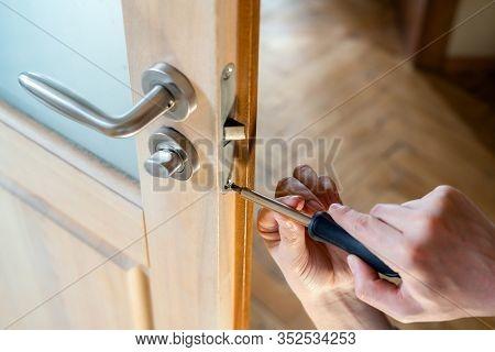 Carpenter Repairing Door Lock. Installing A Door Handle. Handyman Tightening Door Hinge . Hands Of T