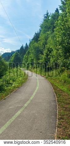Upwarding Asphalted Bystricka Cyklomagistrala Cycle-track With Trees Around And Blue Sky Near Zborov