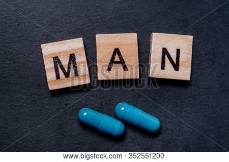 Two Blue Capsules And The Inscription Man. Pills For Mens Health And Sexual Energy On A Black Backgr