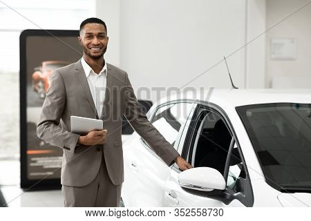 Car Sales. Black Salesman Selling And Showing New Car Standing In Luxury Dealership Center. Selectiv