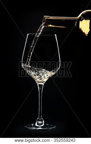 A Close-up Of The Wine Is Poured Into A Glass. Wine Is Poured Into A Glass On A Black Background.