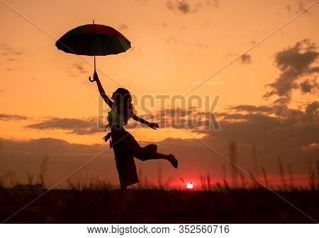 Silhouette Of Carefree Female With Umbrella Dancing In Field Against Cloudy Sunset Sky In Peaceful E