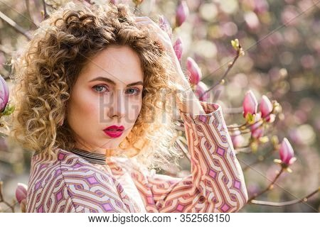 Closeup Portrait Of Blondy Beautiful Girl With Curly Long Hair. Woman Walks In The Garden Of Bloomin