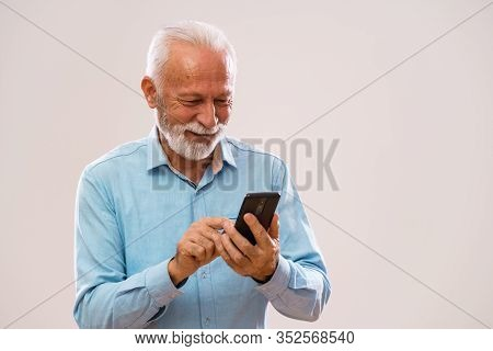 Portrait Of Cheerful Senior Man Who Is Using Smartphone.