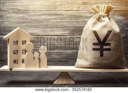 Money Bag With Yen / Yuan And Wooden House On Scales With Family. Fair Value Of Real Estate And Hous