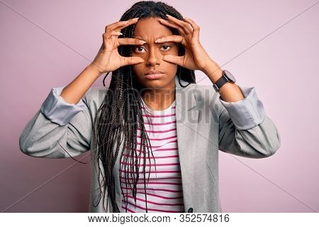 Young african american business woman standing over pink isolated background Trying to open eyes with fingers, sleepy and tired for morning fatigue