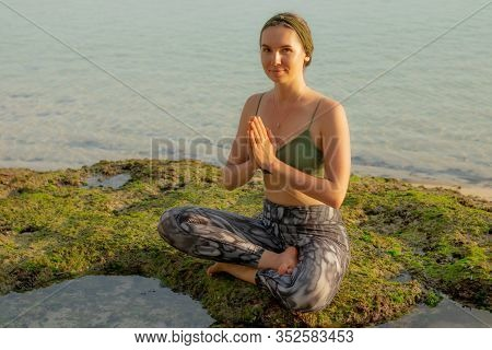 Young Woman, Meditating, Practicing Yoga And Pranayama At The Beach. Sunset Yoga Practice. Hands In