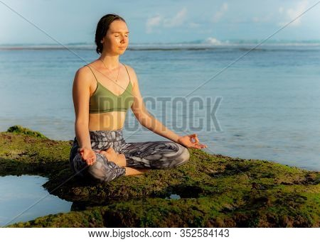 Young Caucasian Woman, Meditating, Practicing Yoga And Pranayama At The Beach. Sunset Yoga Practice.