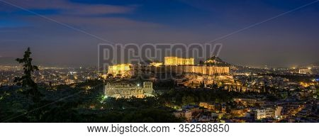 Panorama of Parthenon Temple and Amphiteater are iconic greek tourist landmark at Acropolis of Athens and ancient European civilization architecture. View from Philopappos Hill at night. Greece