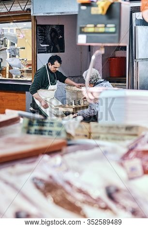 Madrid, Spain - January 10, 2020. Fishmongers Playing Chess In Front Of A Fish Stall. Mercado De La