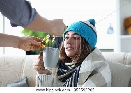 Portrait Of Tired Ill Lady Holding Cup Of Medication. Man Dripping Drops Of Medical Cannabinoid Oil