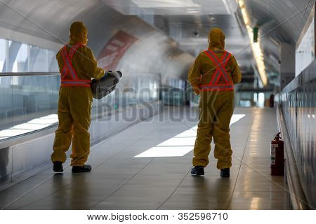 Otopeni, Romania - February 25, 2020: People Wearing Protective Suits Spray Disinfectant Chemicals O
