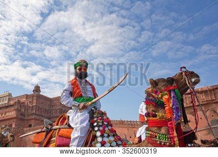 Bikaner, Rajasthan, India - January 11, 2020: Indian Warrior Riding On Camels During Camel Festival