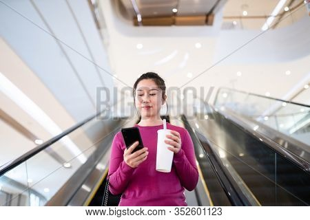 asian female using smart phone at shopping mall