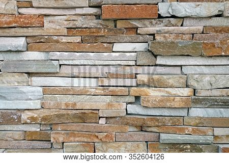 A Colorful Red Tan Brown Slim Cut Slate Rock Wall Close-up
