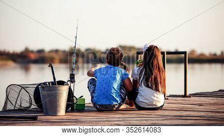 Two Cute Little Friends, Boy And Girl Eating Sandwiches And Fishing On A Lake In A Sunny Summer Day