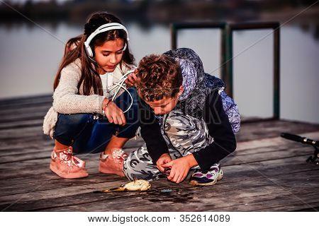 Little Boy Showing His Friend A Fish Caught.
