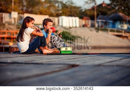 Two Cute Little Friends, Boy And Girl Talking, Drinking Tea, Eating Sandwiches And Fishing On A Lake