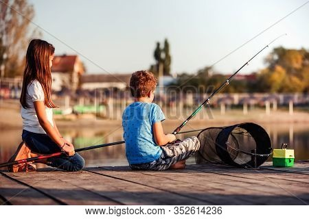 Two Little Friends, Boy And Girl Fishing On A Lake In A Sunny Summer Day