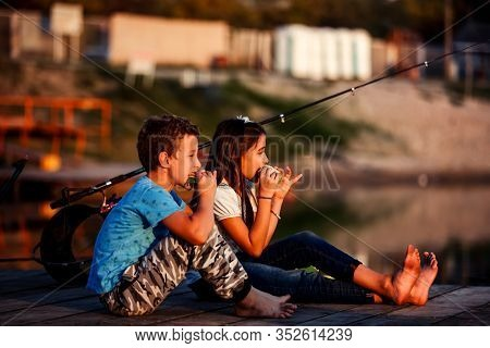 Two Young Cute Boy And Girl Eating Sandwiches And Fishing On A Lake In A Sunny Summer Day