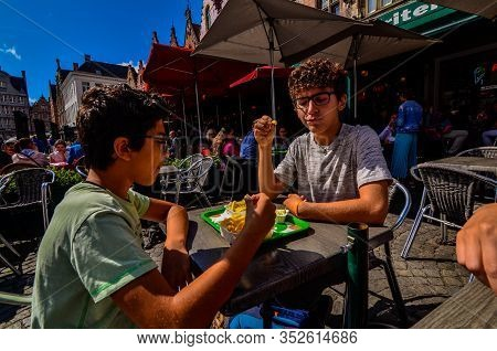 Bruges, Belgium, August 2019. A Chip Shop Overlooking The Touristy Markt Square. Two Caucasian Boys
