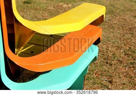 Three Multi Colored Adirondack Chairs Stacked And Waiting For The Spring Weather To Arrive.