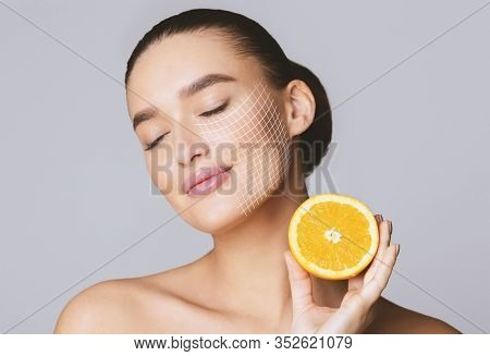 Vitamin C For Skin. Delighted Young Pretty Woman With Closed Eyes Holding Orange Half Over Grey Back