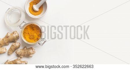 Turmeric Or Curcumin, Curcuma Longa Linn Powder In Glass Jar And Rhizome On White Background, Panora