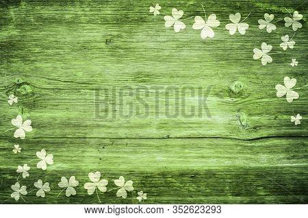 Shamrocks On Green Wooden Table A Symbol Og St. Patricks Day. Bbanner With Corner Border Of Shamrock