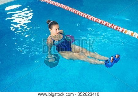 Young Woman Doing Water Aerobics In Indoor Pool, Sporting Concept