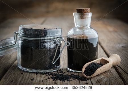 Jar Of Black Cumin Or Roman Coriander Seeds And Black Caraway Oil Bottle. Ingredients For Cooking. A