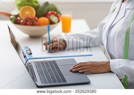 Cropped Of Black Woman Nutritionist Working Online, Using Laptop And Writing Down Client History, Cl