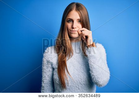 Young beautiful redhead woman wearing casual sweater over isolated blue background mouth and lips shut as zip with fingers. Secret and silent, taboo talking
