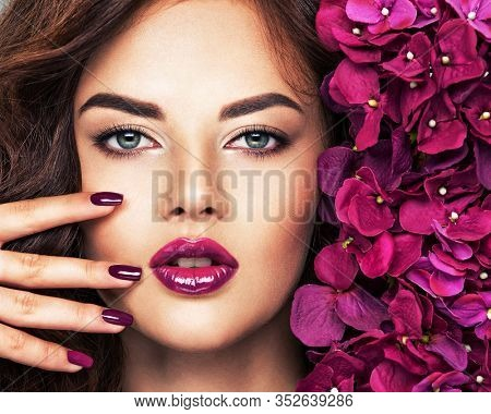 Beautiful  woman with purple make-up of lips and fingernails. Closeup woman's portrait with flowers. Young caucasian gorgeous attractive girl . Model. Vivid make-up. Sexy female. Violet fingernails