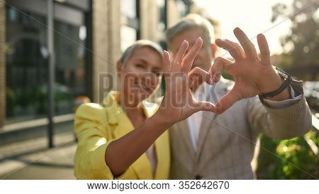 What Is Love. Portrait Of Cute And Cheerful Senior Couple Making A Heart Shape With Their Hands And