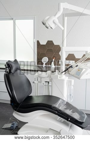 Black leather armchair with medical lamp above and dental equipment and instruments near by inside contemporary dentist office