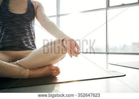 Faceless view of young active woman sitting on mat in pose of lotus while doing relaxing exercise on background of window