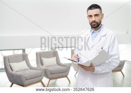 Mid adult dentist in whitecoat making notes in document while standing in front of camera and looking at you in dental clinics