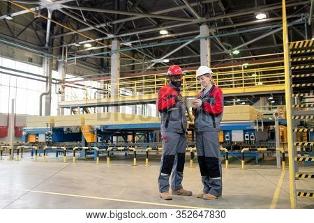 Young interracial colleagues in protective workwear using portable device while planning production volume at factory