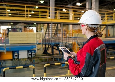 Rear view of busy woman in hardhat and safety goggles using tablet while controlling production line process at factory