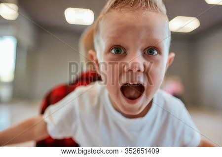 Portrait Of Funny Little Boy In White T-shirt Looking At Camera And Screaming While Having A Choreog