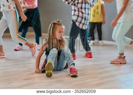 Portrait Of A Little Cute Girl Sitting On The Floor While Having A Choreography Class In The Dance S