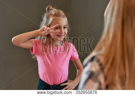 Portrait Of Pretty Little Girl In The Pink T-shirt Showing A Peace Gesture And Smiling While Standin