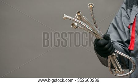 Water Hose In Plumber Hands Close Up Over Gray Background With Copy Space.