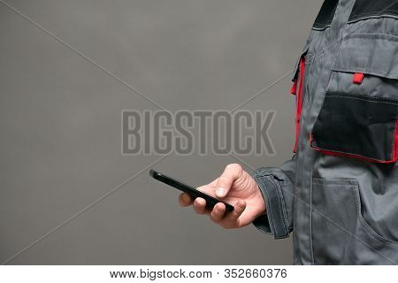 Worker In A Work Clothes Holding In Hand A Mobile Phone On Gray Background With Copy Space.