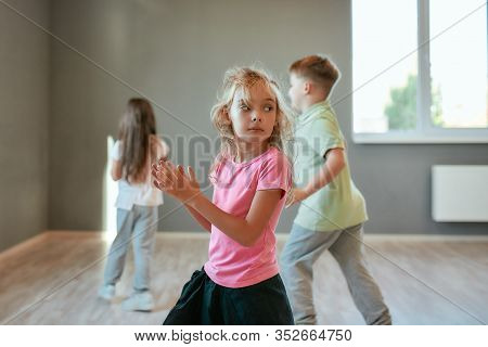 Portrait Of A Little Cute Girl In Fashionable Clothes Dancing While Having A Choreography Class. Gro
