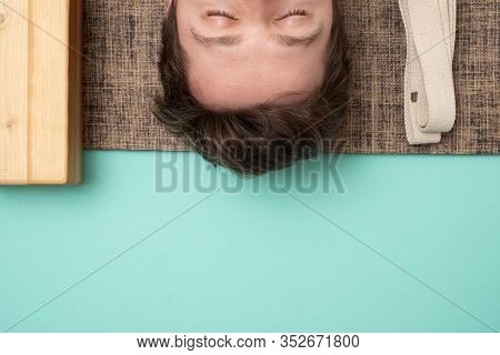 Young Sporty Man Lying In Dead Body Exercise Or Corpse Pose With His Eyes Closed, Savasana Pose